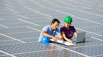 Mann mit Bauplänen und Frau mit Bauhelm auf Solarfeld, Frau bedient Laptop