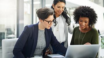 Drei Frauen an Schreibtisch, schauen gemeinsam auf Laptop