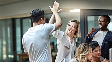 Gruppe Männer und Frauen vor PC, Mann und Frau klatschen sich ab