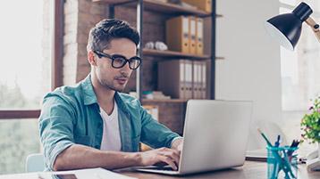 Mann sitzt an Schreibtisch, arbeitet an Laptop