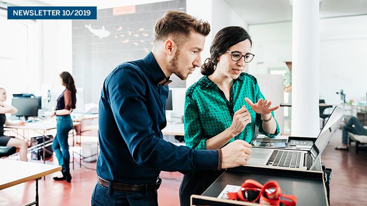 Ein Mann und eine Frau schauen gemeinsam auf einen Laptop.