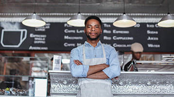 Ein Mann mit Schürze steht mit verschränkten Armen vor der Theke in einem Café.