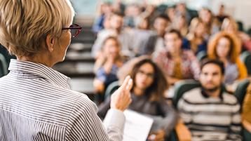 Eine Frau steht vor Studierenden in einem Hörsaal.