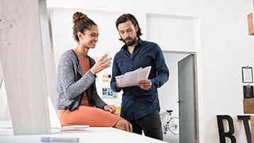 Eine Frau und ein Mann betrachten gemeinsam Unterlagen.