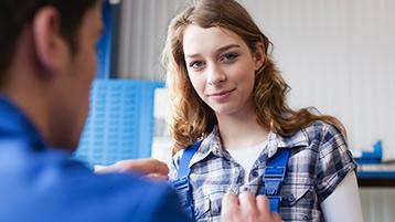 Eine junge Frau im Blaumann schaut in die Kamera.