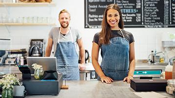 Ein Mann und eine Frau stehen in einem Café hinter der Theke mit Kasse.
