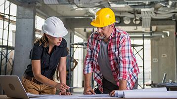 Eine Handwerkerin und ein Handwerker besprechen Unterlagen.