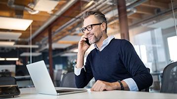 Ein Mann sitzt vor einem Laptop und telefoniert mit einem Smartphone.