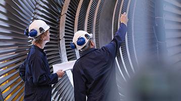 Zwei Männer mit Schutzhelmen stehen vor einer technischen Anlage.