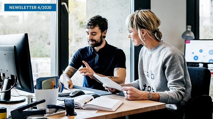 Ein junger Mann und eine junge Frau sitzen gemeinsam an einem Schreibtisch.