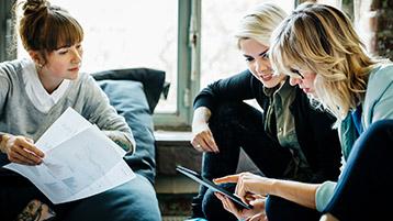 Junge Frauen schauen sich gemeinsam Dokumente an.